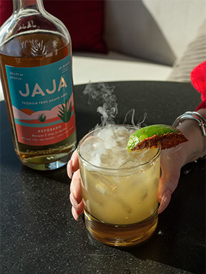Bottle of JAJA liquor with woman's hand holding cocktail with lime garnish.