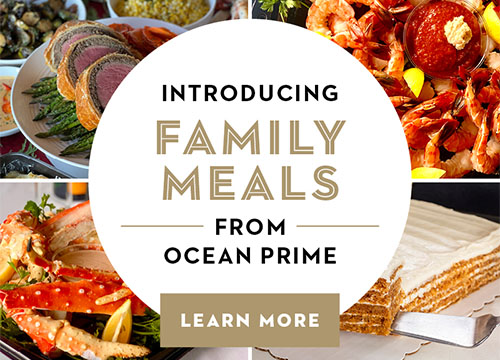 Background images of seafood and signature Ocean Prime dishes like sushi, shrimp, crab legs and carrot cake. Promotional text reads Introducing Family Meals from Ocean Prime. Learn More button links to Ocean Prime Holiday Packages page.